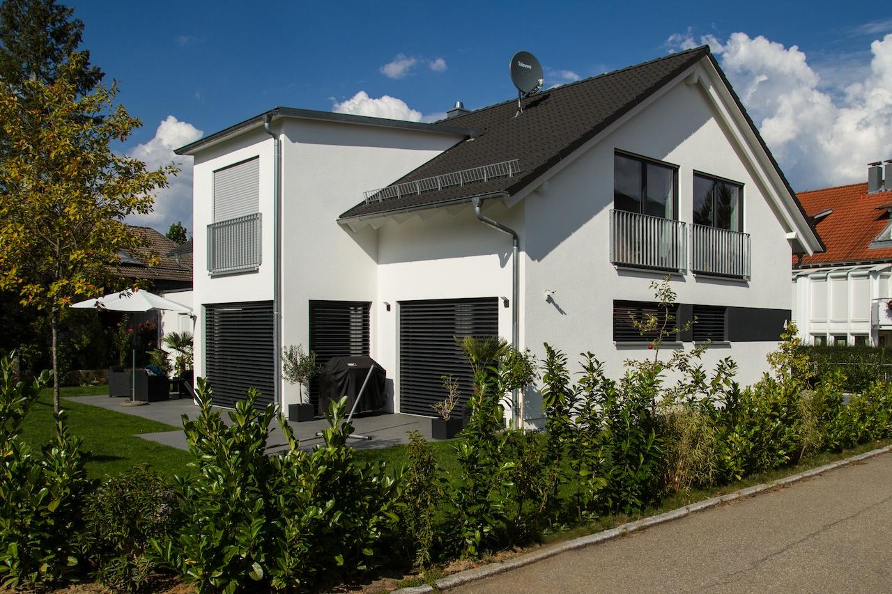 Einfamilienhaus mit anthrazitfarbigem Satteldach und klassischem Dachüberstand, Flachdachgaube und Erker
