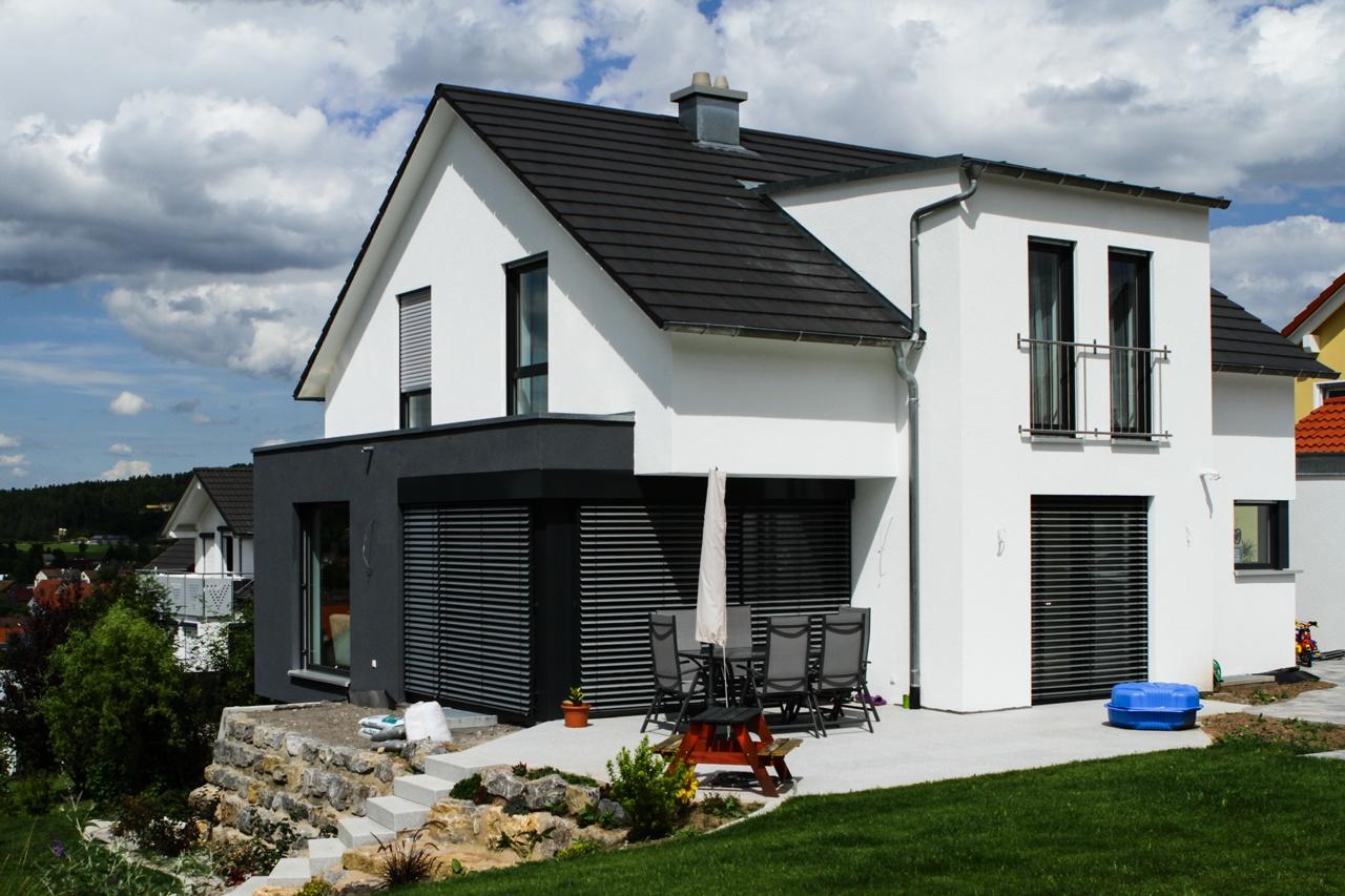 Einfamilienhaus mit Satteldach und modernem Dachüberstand, anthrazitfarbigem Erker und Flachdachgaube