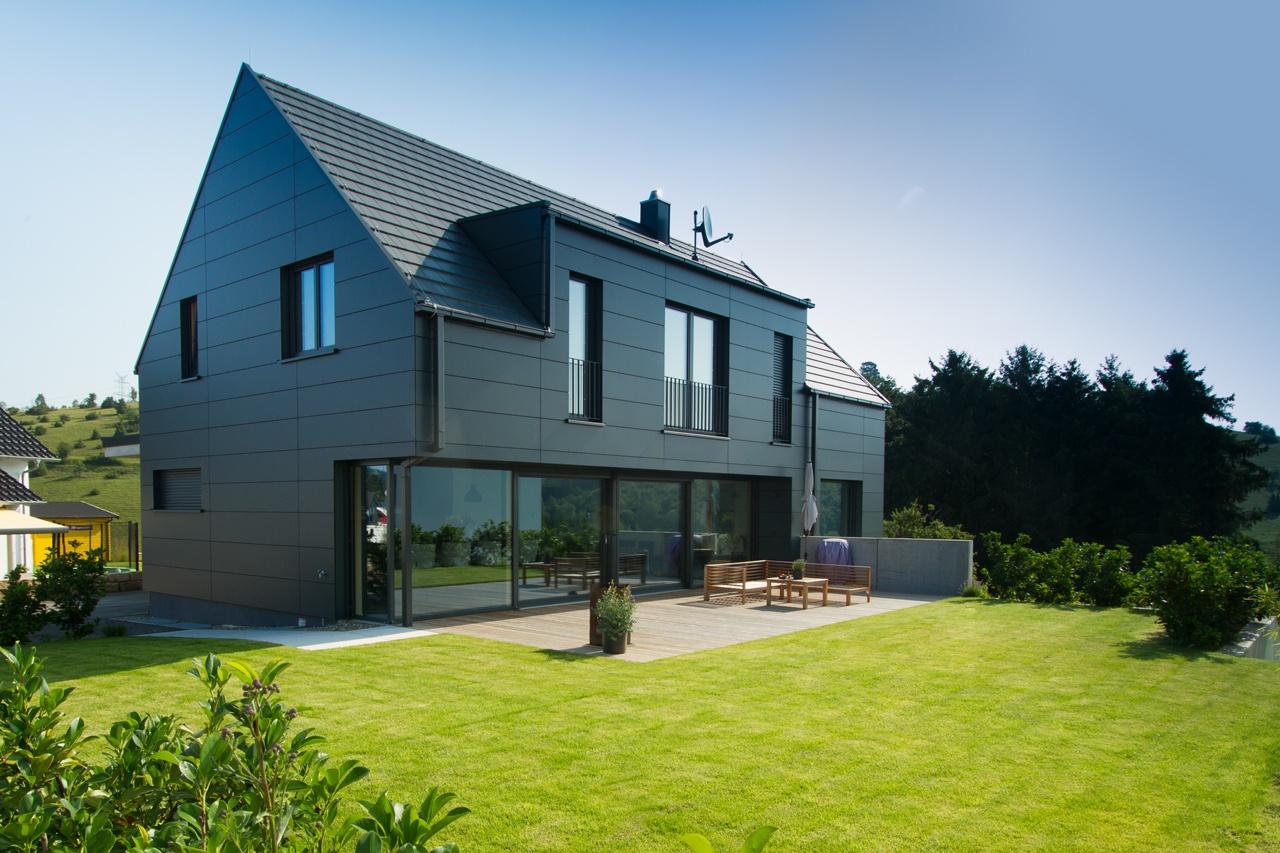 Einfamilienhaus mit Satteldach, dunklen Fasadenpaneelen, stehender Gaube, großem Fensterelement